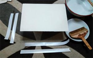 水刷毛で引いた水分が紙に浸透するまでの間に、水張りテープを4辺分ちぎります。